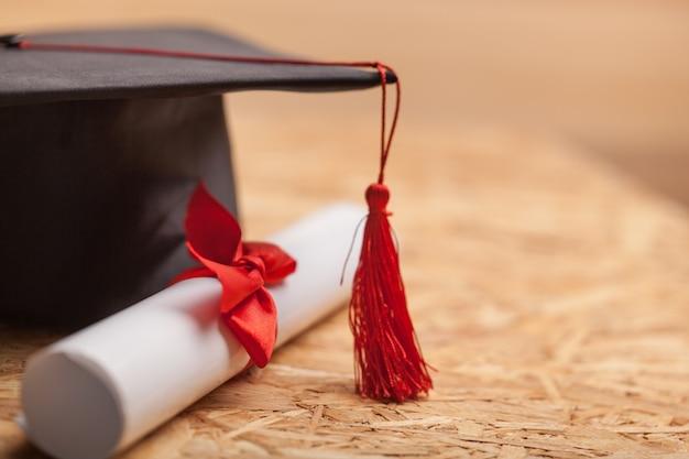 Chapéu de formatura e diploma em fundo de madeira