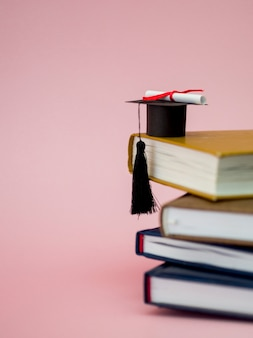 Chapéu de formatura e diploma em livros diferentes, com espaço de cópia