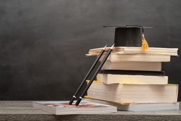 Chapéu de formatura, livros e lápis em cima da mesa