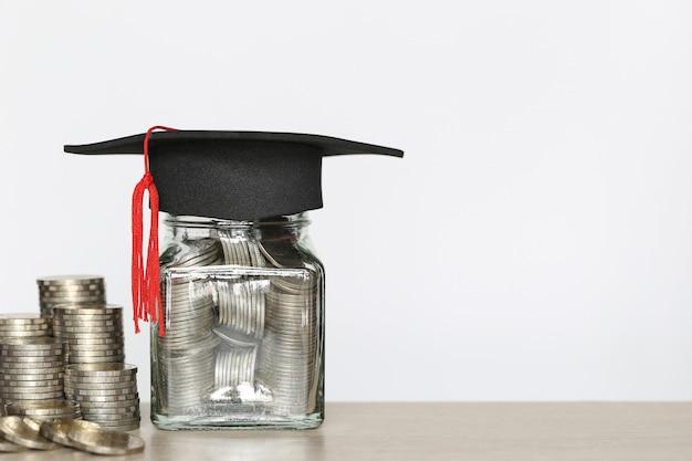 Chapéu de formatura na garrafa de vidro com pilha de dinheiro moedas no wtite, poupar dinheiro para a educação