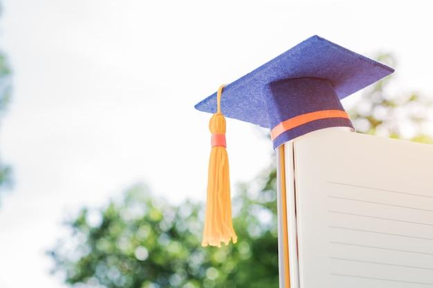 Chapéu de formatura no caderno branco com campeão mostrar sucesso na educação internacional