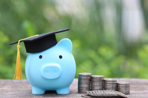 Chapéu de formatura no cofrinho azul com pilha de moedas e dinheiro no espaço verde da natureza economizando dinheiro para o conceito de educação