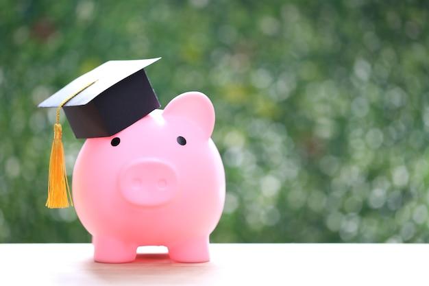 Chapéu de formatura no cofrinho com fundo verde da natureza, economizando dinheiro para o conceito de educação
