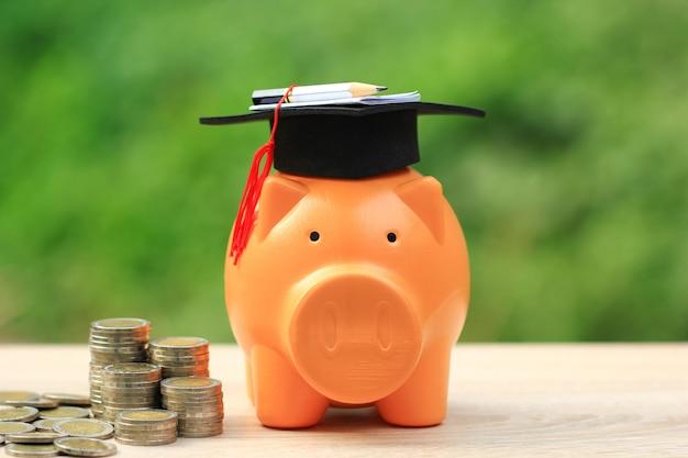 Chapéu de formatura no cofrinho com pilha de dinheiro moedas sobre fundo verde, poupar dinheiro para o conceito de educação