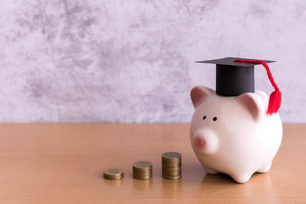 Chapéu de formatura no cofrinho com pilha de moedas e dinheiro na mesa, economizando dinheiro para o conceito de educação