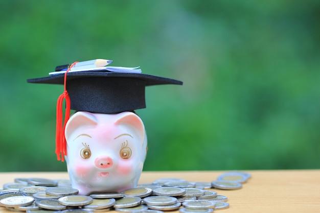 Chapéu de formatura no cofrinho rosa com pilha de dinheiro moedas sobre fundo verde, poupar dinheiro para o conceito de educação