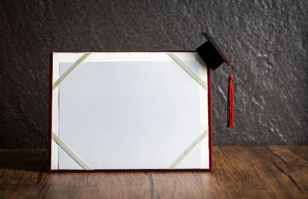 Chapéu de formatura no conceito de educação de certificado de graduação em madeira com fundo escuro