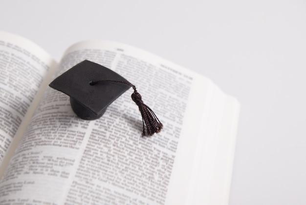 Chapéu de graduação nas páginas da bíblia sagrada