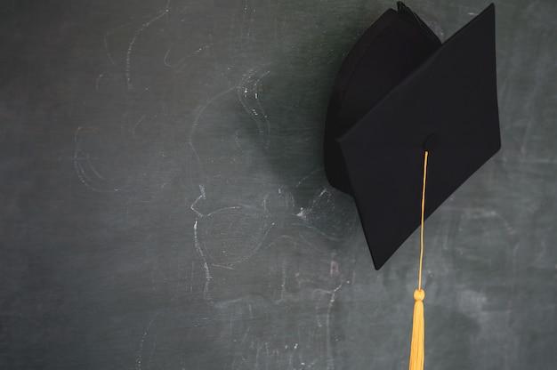 Chapéu de graduados preto pendurado no quadro-negro