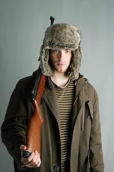 Chapéu de inverno de pele de homem caçador segurando a arma rifle