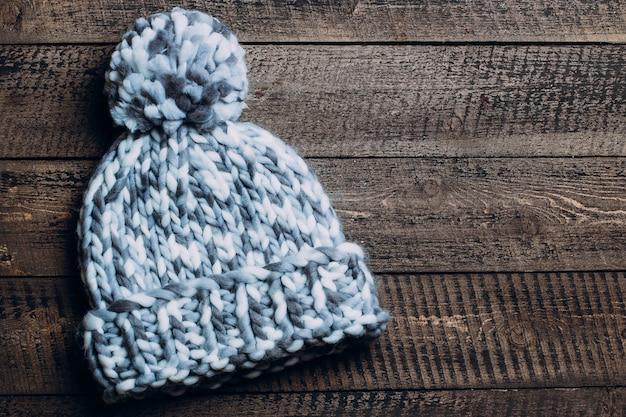 Chapéu de inverno e luvas na mesa de madeira