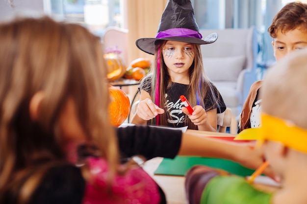 Chapéu de mago. linda garota de cabelos escuros usando um chapéu preto de mago para o halloween, brincando com seus amigos no jardim de infância