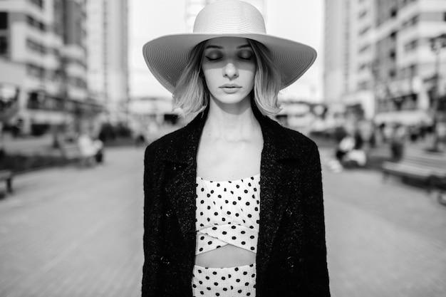 Chapéu de mulher loira elegante e elegante de cabelo curto posando sobre o fundo da rua