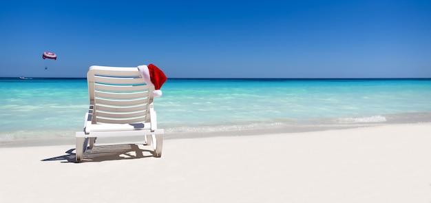 Chapéu de natal em espreguiçadeira em praia tropical com areia branca e água do mar azul-turquesa