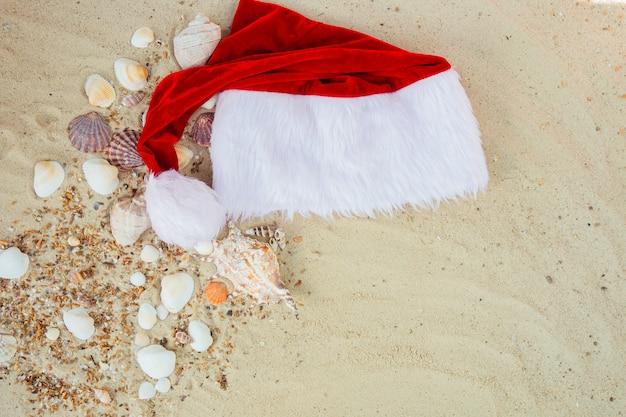 Chapéu de natal na praia. chapéu de papai noel na areia perto de conchas.