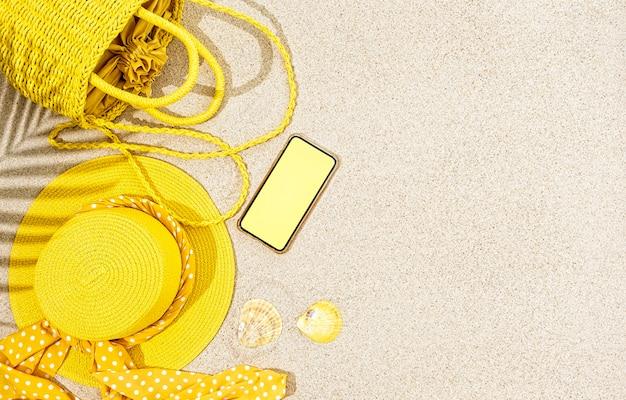 Chapéu de palha amarelo, bolsa, conchas do mar e telefone como pano de fundo do conceito de verão, espaço de cópia, postura plana