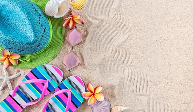 Chapéu de palha azul e verde e chinelos coloridos na areia com conchas e flores de frangipani.
