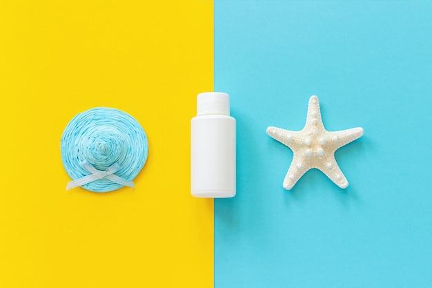 Chapéu de palha azul, estrela do mar e tubo branco, garrafa de protetor solar em fundo de papel amarelo e azul