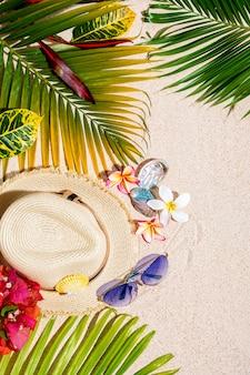 Chapéu de palha bege com óculos de sol azuis, conchas do mar colorido, flores de frangipani e folhas de palmeira verde na areia.
