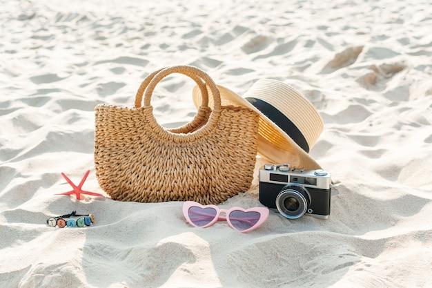 Chapéu de palha, bolsa, óculos escuros, coral e câmera na areia na praia tropical. conceito de férias de verão