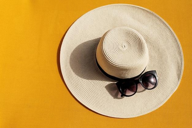 Chapéu de palha bonito com óculos de sol no fundo vívido vibrante amarelo. vista do topo. conceito de férias de viagem de verão.