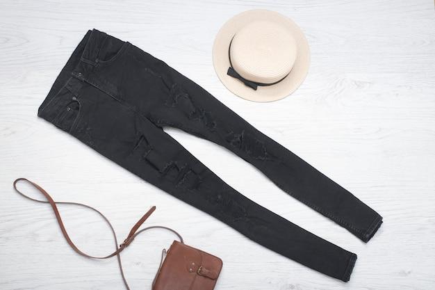 Chapéu de palha, calça jeans preta, bolsa.