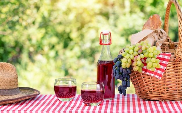 Chapéu de palha, cesta com uvas e suco na toalha de mesa quadriculada vermelha