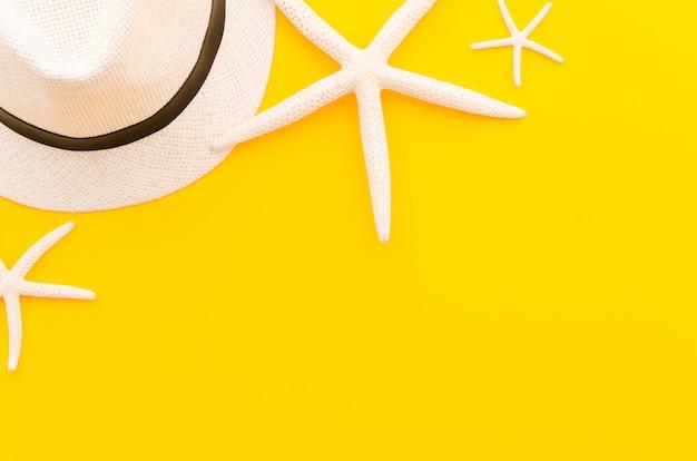 Chapéu de palha com estrelas do mar na mesa amarela