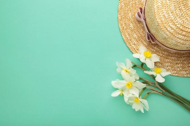 Chapéu de palha com flores da primavera na superfície da hortelã