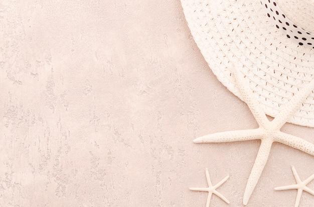 Chapéu de palha de mulher com estrelas do mar na mesa