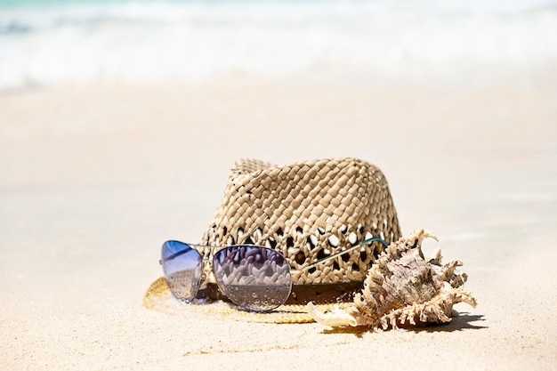 Chapéu de palha de verão, concha do mar e óculos de sol na costa do mar, conceito de férias tropicais de verão