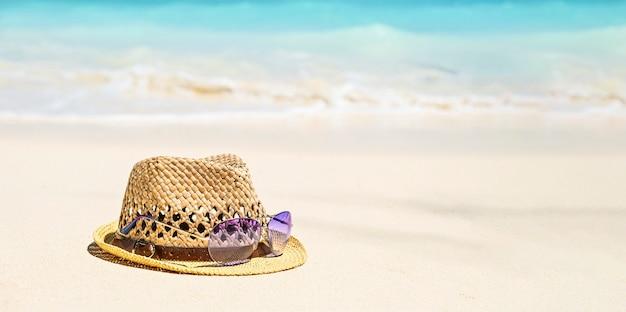 Chapéu de palha de verão e óculos de sol na costa, conceito de férias tropicais de verão