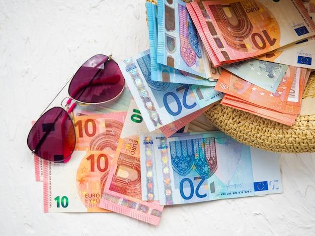 Chapéu de palha, dinheiro, cartões bancários, óculos brilho