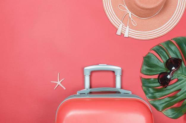 Chapéu de palha do verão, estrela do mar mala de viagem e óculos de sol em vermelho