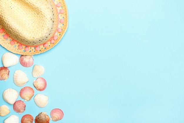 Chapéu de palha e conchas sobre um fundo azul