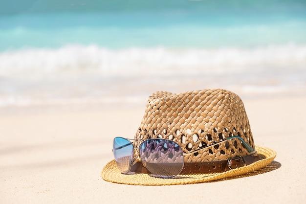 Chapéu de palha e óculos de sol azuis na beira-mar com mar azul