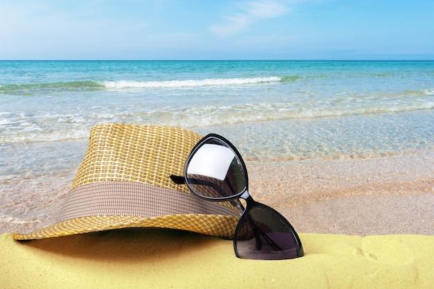 Chapéu de palha e óculos de sol em uma vista frontal de praia de areia