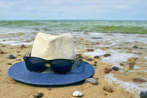 Chapéu de palha e óculos de sol encontram-se em uma praia arenosa com seixos.