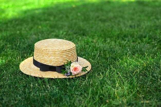 Chapéu de palha elegante com flores frescas colocar em um gramado verde