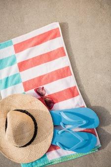 Chapéu de palha, falhanço de aleta azul e óculos de sol mantido no cobertor da praia