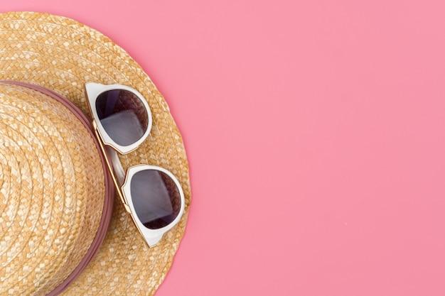 Chapéu de palha feminino e óculos de sol para vista superior de férias de praia