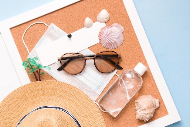 Chapéu de palha, gel desinfetante, máscara facial médica, palmeira, óculos de sol e conchas de marisco no quadro de cortiça