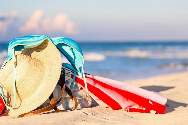 Chapéu de palha, guarda-chuva e biquíni de maiô azul com bolsa de praia na praia