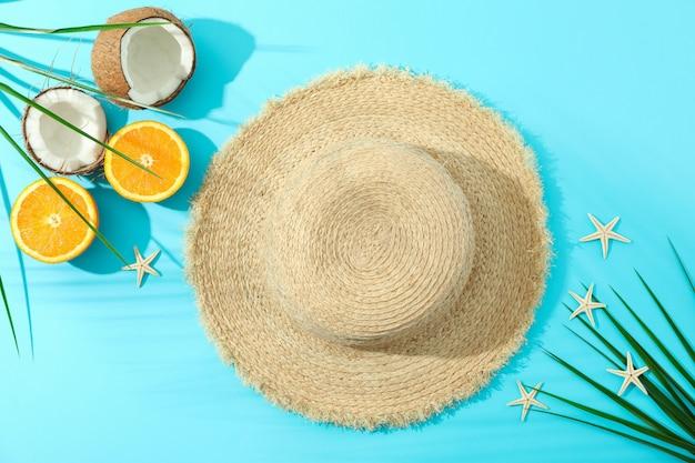 Chapéu de palha, laranjas, cocos, folhas de palmeira e estrelas do mar sobre fundo de cor, espaço para texto e vista superior. conceito de férias de verão