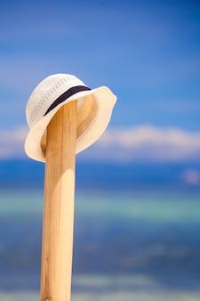 Chapéu de palha na cerca de madeira na praia de areia branca com vista para o mar