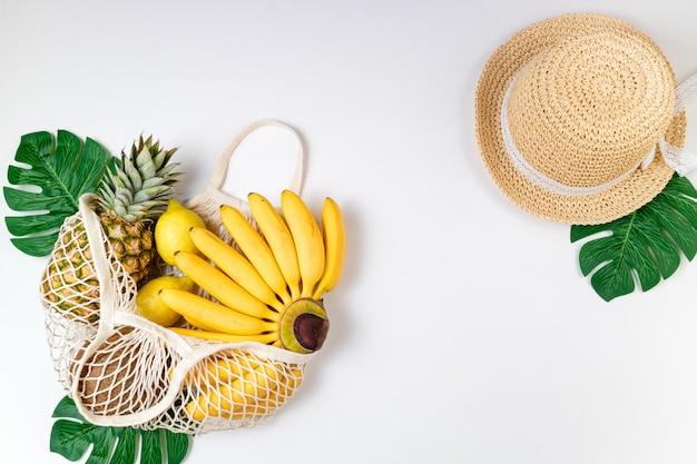 Chapéu de palha na moda feminina moda composição de verão, saco ecológico com frutas tropicais