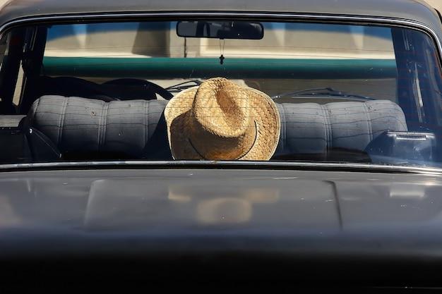 Chapéu de palha no banco de trás do carro retrô. fim preto velho do automóvel acima. fundo minimalista com transporte de viajante romântico.