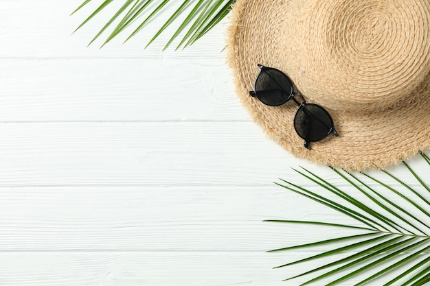 Chapéu de palha, óculos de sol e folhas de palmeira em fundo branco de madeira, espaço para texto e vista superior. conceito de férias de verão