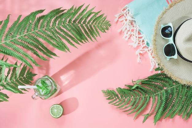 Chapéu de palha, óculos de sol, toalha, folha de samambaia e bebidas refrescantes com limão rosa pastel