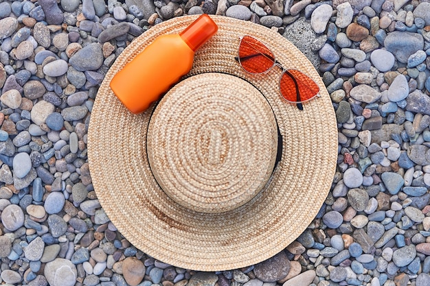 Chapéu de palha, óculos de sol vermelhos brilhantes e uma garrafa de protetor solar para proteção solar